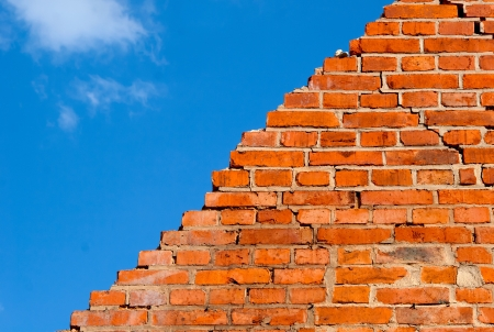 pared rota: Pared de ladrillos rotos contra el cielo azul