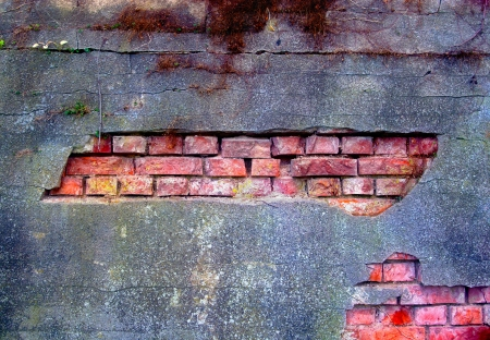 Old and damaged plaster on the brick wall photo