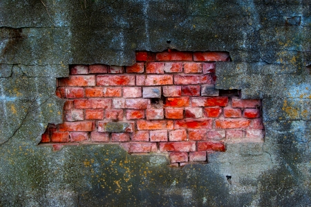 Old and damaged plaster on a red brick wall photo