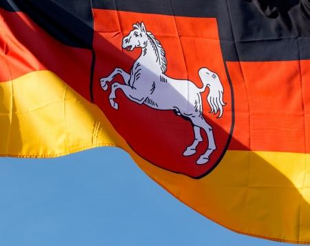 푸른 하늘에 대하여 니더 작센의 독일 국기 스톡 콘텐츠