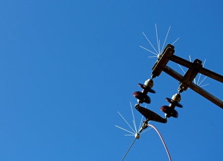 isolators: High-voltage electrical insulator of electric line against the blue sky