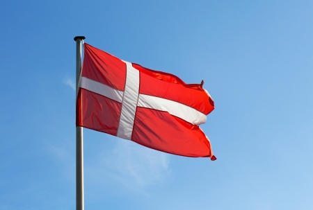 Flag of Denmark against blue sky photo