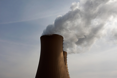 Nuclear plant and smoke against a sky photo