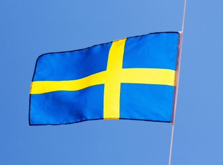 the swedish flag: Swedish flag in the wind against the sky Stock Photo