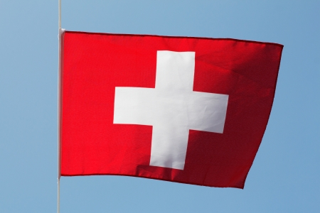 Swiss flag in the wind against the sky photo