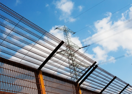 fencing wire:  Barrier fence and Electricity pylon against the blue sky Stock Photo