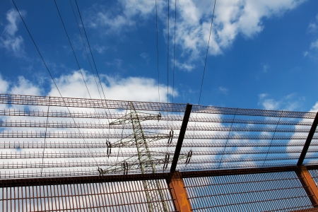 Electricity pylon and barrier fence against the blue sky photo