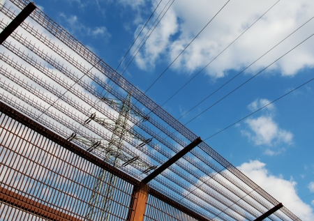 fencing wire: Electricity pylon and barrier fence against  blue sky Stock Photo