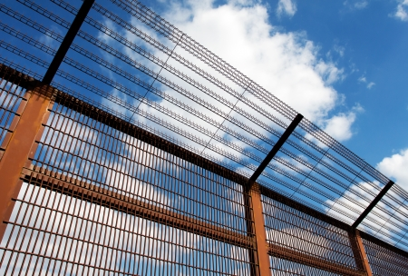 Security fence against the blue sky