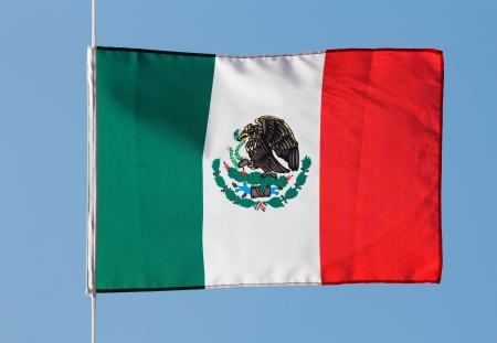 mexican flag: Mexican flag in wind against the blue sky