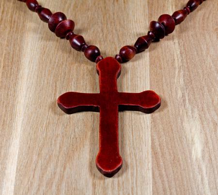 cruz cristiana: Cruz cristiana se extiende sobre una superficie de madera Foto de archivo