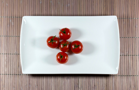 straw mat: Tomatoes on a rectangular plate standing on a straw mat