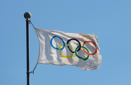 olympiad: Olympic flag against a blue sky in the sunlight