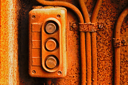 Old electric switch on the rusty iron wall photo