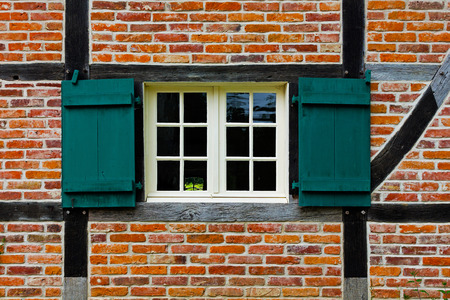 half timbered house: Window with shutters in brick wall of the half timbered house