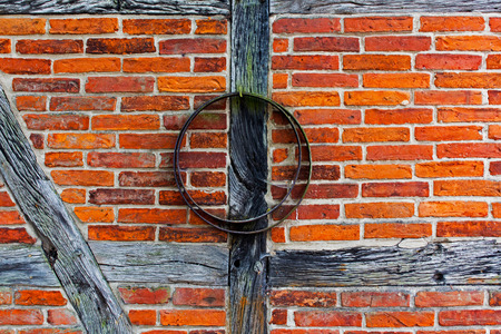 Brick wall of the half timbered house and iron hoop photo