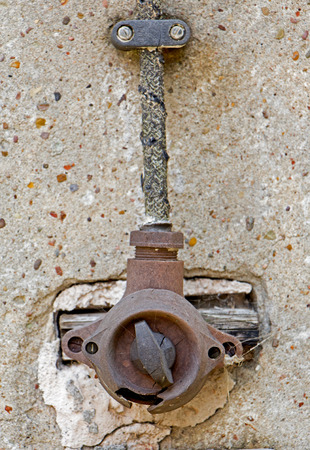 Old electric switch on the concrete wall photo