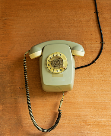 hablando por celular: Teléfono viejo con un cable en la pared