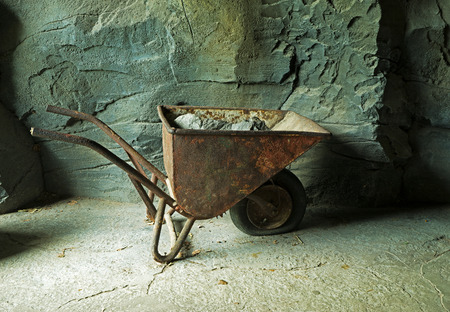 ore: Old rusty wheelbarrow with ore at the mine at the stone wall
