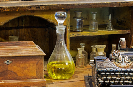 Old decanter with a reagent and typewriter on a dusty table