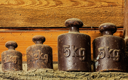calibration: The old calibration weights in a shed at the wooden wall
