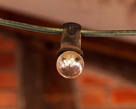 matt: Light bulb on the cable against brick wall