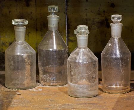 De oude reagens glazen flessen op een stoffige tafel Stockfoto