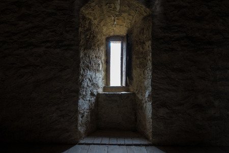 Donkere kamer met stenen muren en raam