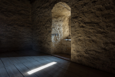 ancient prison: Dark room with stone walls window and wooden staircase Stock Photo