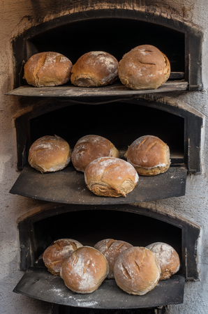 baked bread: Freshly baked bread in a wood-fired stone oven