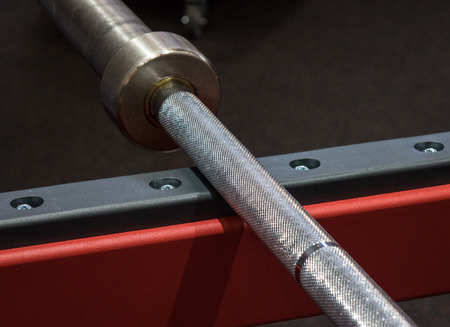 fitness center: weight lifting bar on the rack  in a  fitness center