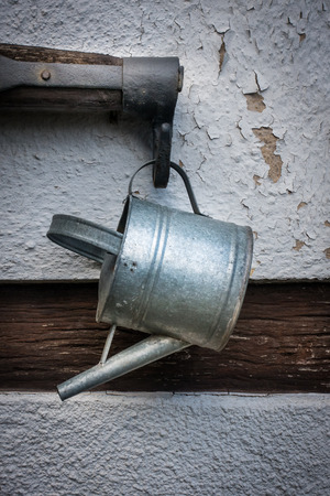 bailer: The old watering can and rocker on wall of  farmhouse Stock Photo