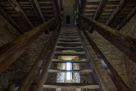 inwardly: Dark room with stone walls window and wooden staircase Stock Photo