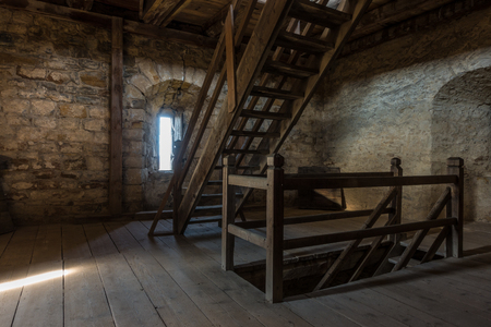 inwardly: Dark room with stone walls window and wooden staircase Editorial