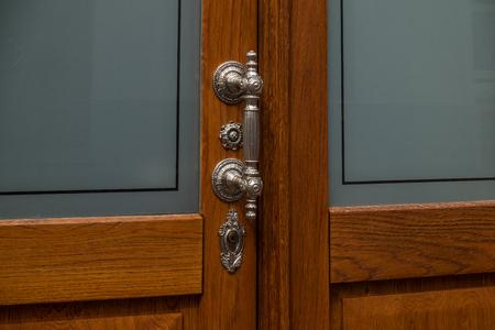 doorhandle: The old, metal doorhandle of a wooden door .