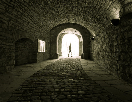 inwardly: Dark stone streets  in an old town  and people .