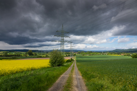voltage gray: Electricity pylon in the field, Germany .