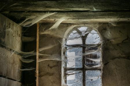 lattice window: The  window with cobwebs of an old farmhouse inside Stock Photo