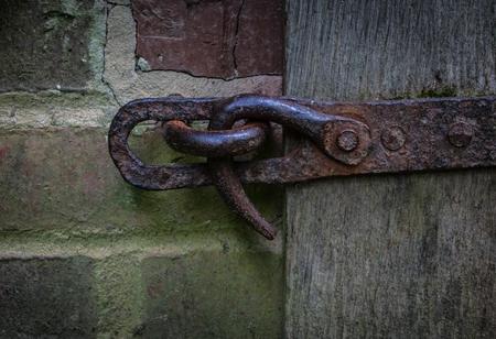 deadbolt: The iron latch on a wooden door.
