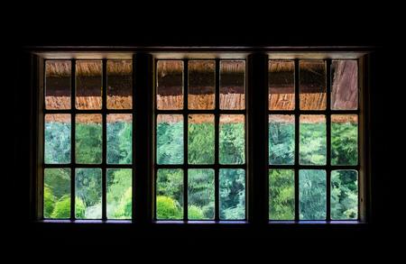 lattice window: The wall and window of an old farmhouse inside . Stock Photo