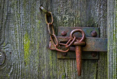 The iron latch on a wooden door.