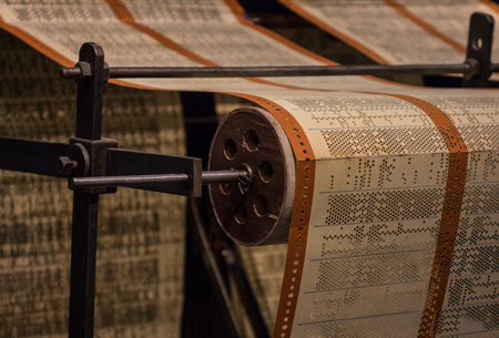 ciphering: The perforated paper tape of an old device. Stock Photo
