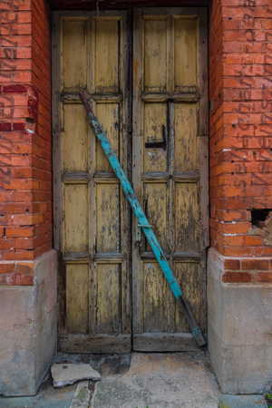 The wooden door of dilapidated building in a city. Stock Photo