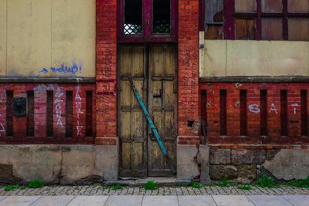 The wooden door of dilapidated building in a city. Stok Fotoğraf