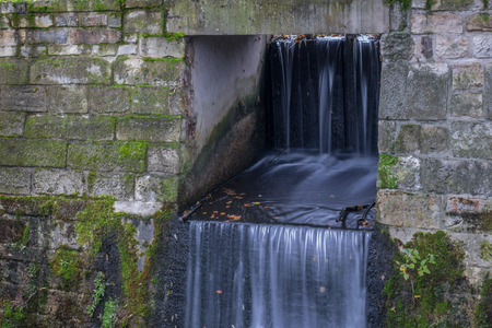 The waterfall out dam of city pond in Bueckeburg, Germany. Stock Photo