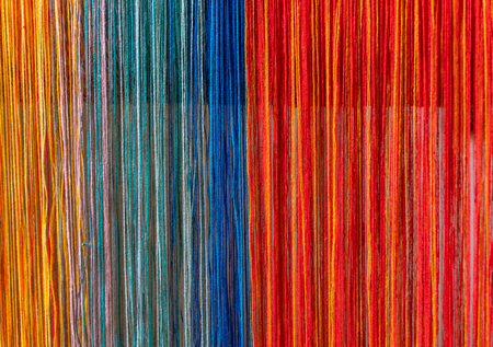 Colored threads of an ancient wooden loom . Imagens
