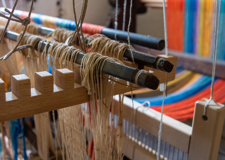 Colored threads of an ancient wooden loom . Stock Photo