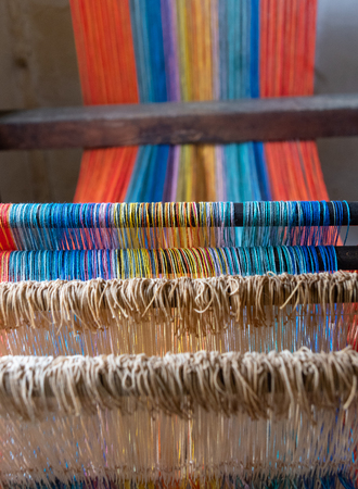 Colored threads of an ancient wooden loom . Standard-Bild - 117911212
