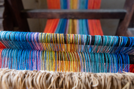 Colored threads of an ancient wooden loom . Standard-Bild