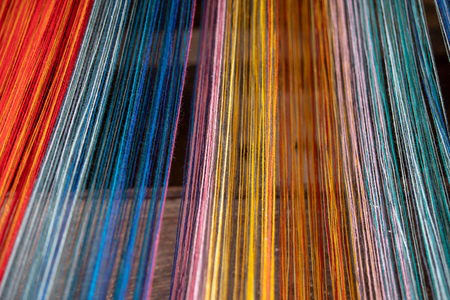 Colored threads of an ancient wooden loom . Standard-Bild - 117911816